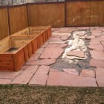 Flagstone pathways with blank spaces where raised beds will sit.